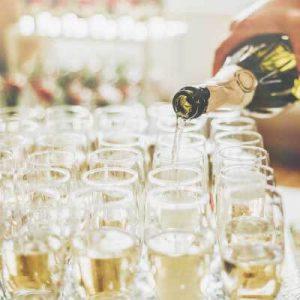 Ein Tablet mit Sektgläsern wird aus einer Sektflasche befüllt - Dramburg+Hertwig Getränkefachhandel